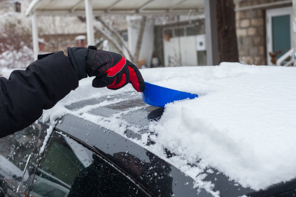 Man Cleaning Snow off Car Roof
